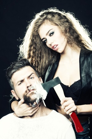 barber background: Portrait closeup couple of long-haired young sensual woman shaving handsome bearded grey-haired man with chopper and foam looking forward on grey background, vertical picture