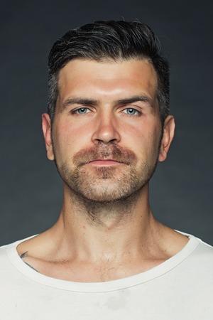 강모와 눈썹 한 잘 생긴 관능적 인 면도 남자의 초상화 근접 촬영 모델 회색 배경, 세로 그림에 스튜디오에서 찾고 제기 스톡 콘텐츠