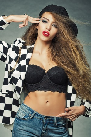 Portrait of attractive woman with fly-away wavy long hair wearing black and white cardigan cap underwire bra jeans shot-head gesture posing eyes shut in studio on grey background, vertical picture