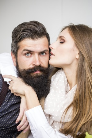emotional couple: Closeup view on one attractive stylish emotional couple of young woman and senior man with long black beard embracing sitting close to each other intdoor in cafe, vertical picture