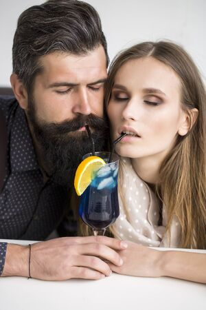 emotional couple: Closeup view on one attractive stylish emotional couple of young woman and senior man with long black beard drinking blue cocktail in glass with straw and orange slice sitting intdoor, vertical photo
