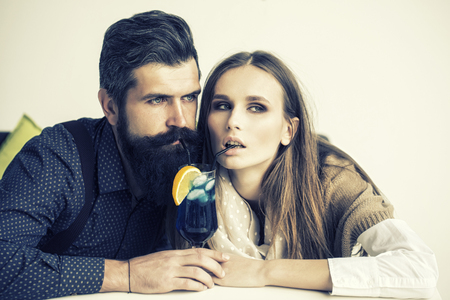 emotional couple: Closeup view on one attractive stylish emotional couple of young woman and senior man with long black beard drinking blue cocktail in glass with straw and orange slice intdoor, horizontal photo