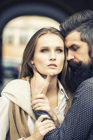 boy lady: One beautiful stylish couple of young woman and man with long black beard standing close to each other outdoor in autumn street near arch, vertical picture