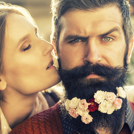 male and female: Young beautiful couple of woman kissing man with long black beard with many little white red and pink flowers sunny day outdoor on natural background, square picture