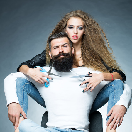 looking forward: Couple of long-haired young beautiful woman holding two pairs of scissors sitting behind handsome bearded grey-haired man with moustache both looking forward on grey background, square picture Stock Photo