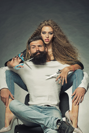 Couple of long-haired young beautiful woman holding two pairs of scissors sitting behind handsome bearded grey-haired man with moustache both looking forward on grey background, vertical picture Stockfoto