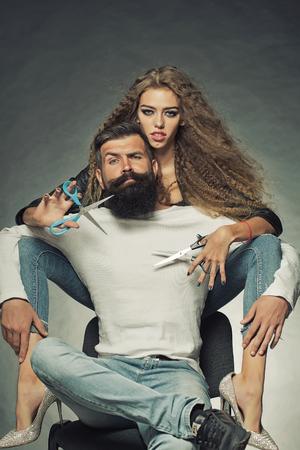 Pareja de pelo largo joven y bella mujer que sostiene dos pares de tijeras que se sientan detrás del hombre de pelo gris con barba guapo con bigote tanto mirando hacia adelante sobre fondo gris, imagen vertical Foto de archivo - 47343799