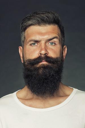 Portret close-up van een knappe sensuele grijsharige ongeschoren gebruinde man met een lange baard en snor model verheugen in de studio op een grijze achtergrond, verticale foto