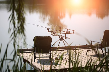 spinning reel: Carp spinning reel angling rods on pod standing between two black comfortable armchairs on wooden pier with beautiful picturesque view summer vacation tranquility, horizontal picture Stock Photo