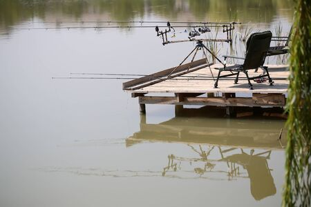 portative: Wooden pier with black armchair two fishing rods laying on floor and spinning tackle on standing pod with reflection on surface of river water summer relaxing weekends, horizontal picture Stock Photo