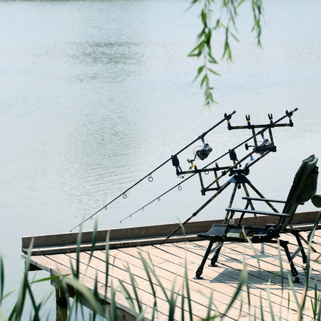 sportfishing: Modern equipment for angling portative black armchair on pier in river in summer time at morning on natural background leisure recreation male activity sportfishing, square picture