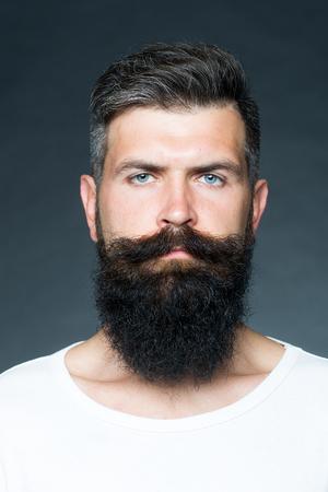 sensual: Retrato del primer de un hombre guapo sensual de pelo gris sin afeitar bronceada con una larga barba y bigote modelo mirando hacia adelante en el estudio sobre fondo gris, imagen vertical Foto de archivo