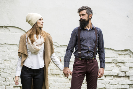stylish couple: One beautiful stylish emotional couple of young woman and senior man with long black beard standing close to each other outdoor in autumn street on white brick wall background, horizontal picture