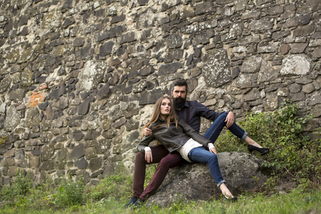 stylish boy: Young beautiful tender modern stylish couple of slim woman and man with long lush beard sitting on rock with grass near big stony grey wall on outdoor autumn background, horizontal picture Stock Photo