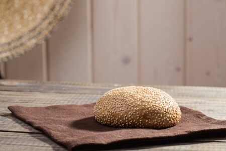 sesame seed bun: Rustic still life photo of traditional round fresh baked organic white wholegrain wheat loaf of homemade bread sesame seed bun lying on brown brat on wooden background, horizontal picture