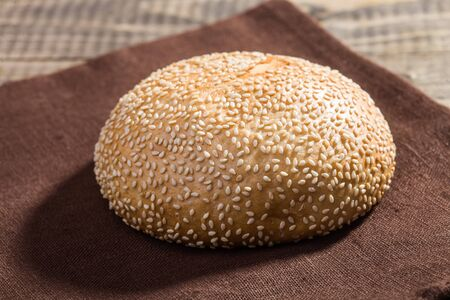 Closeup photo of traditional round fresh baked organic white wholegrain wheat loaf of homemade bread bun topped with sesame seeds lying on brown brat on rustic wooden background, horizontal picture 免版税图像