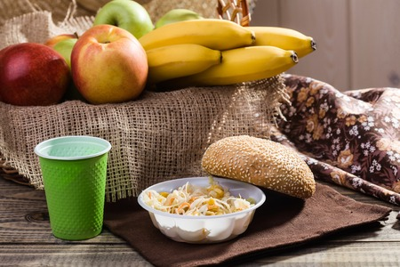 brat: Country still life with fresh baked sesame seed bun salad fruit bananas apples red green in basket and disposable tableware lying on brown brat on rustic wooden background, horizontal picture Stock Photo