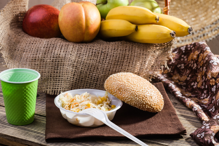 sesame seed bun: Country still life disposable green cup white fork salad sesame seed bun bananas apples peaches red green in basket lying on brown sackcloth on rustic wooden background, horizontal picture Stock Photo