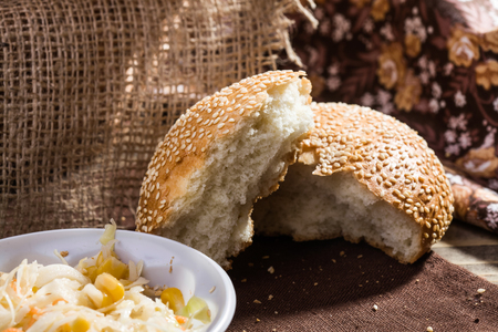 sesame seed bun: Photo closeup two pieces of sesame seed bun crumbs and vegetable salad in white disposable cutlery on brown cloth over rustic sackcloth background, horizontal picture Stock Photo