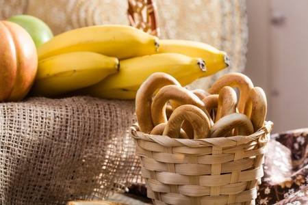brown banana: Photo still life closeup basket full of hard oval cracknels with fresh fruit piece red peach green apple and yellow bananas lying on brown sackcloth on blurred background, horizontal picture