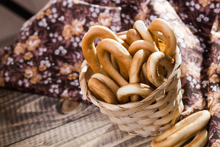 heaped: Photo top view of hard oval cracknels in basket heaped high with some bagels lying on wooden table over blurred flowery cloth rustic background, horizontal picture Stock Photo