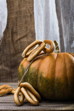 hard bound: Photo closeup autumn still life one big whole fresh orange pumpkin with bunches of hard oval cracknels bind with string on wooden table on blurred rustic background, vertical picture