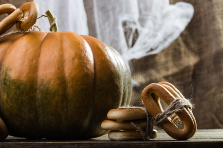 hard bound: Photo closeup autumn still life one big whole fresh orange pumpkin with bunches of hard oval cracknels bind with string on wooden table on blurred rustic background, horizontal picture