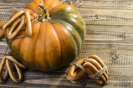 hard bound: Photo top view closeup rustic autumn still life one big whole fresh orange pumpkin with bunches of hard oval cracknels bind with string on wooden table on timber background, horizontal picture Stock Photo