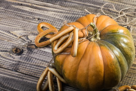 hard bound: Photo top view closeup rustic autumn still life one big whole fresh orange pumpkin with bunches of hard oval cracknels bind with long string on wooden table on timber background, horizontal picture Stock Photo