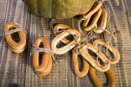 bind: Top distant view closeup rustic autumn still life one big partial fresh orange pumpkin with bunches of hard oval cracknels bind with string on wooden table on timber background, horizontal picture