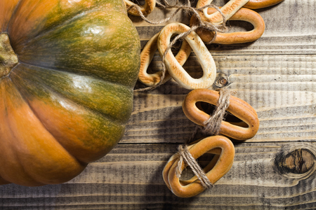 string top: Top distant view closeup rustic autumn still life one big partial fresh orange pumpkin with bunches of hard oval cracknels bind with string on wooden table on timber background, horizontal picture