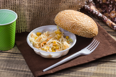 brat: Country still life with fresh baked sesame seed bun vegetable salad with disposable green cup and white fork lying on brown brat on rustic wooden background, horizontal picture