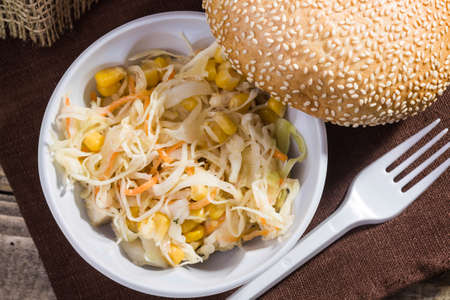 brat: Closeup top view still life fresh baked white wheat bun topped with sesame seeds cabbage and corn salad disposable cutlery lying on brown brat on rustic background, horizontal picture