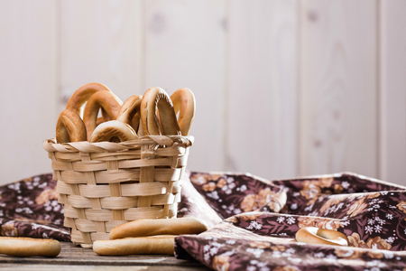 heaped: Photo still life closeup basket full of delicious hard oval cracknels heaped high with some bagels lying on table near flowery cloth over blurred wooden rustic background, horizontal picture