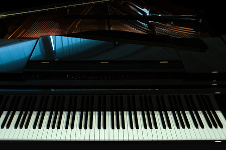 acoustically: Closeup view of one beautiful big shiny black open piano forte with white key board standing in studio with no people, horizontal picture