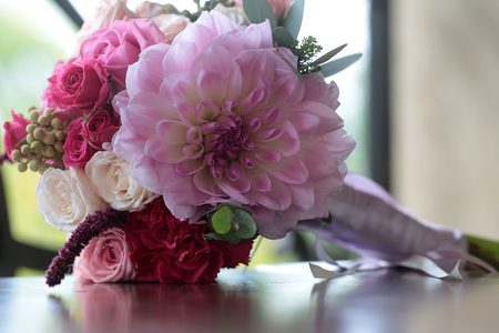 Closeup view of one beautiful fresh colorful mixed wedding bouquet with different flowers pink lilac violet purple colors with bow indoor, horizontal picture
