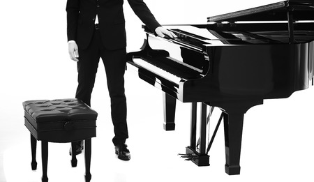 acoustically: Closeup view of one beautiful big shiny black open piano forte with white key board and male musician standing in studio isolated on white background, horizontal picture