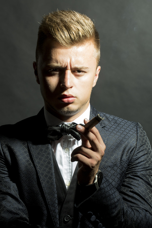 upper half: Young sexy handsome confident frown man model with stylish haircut dressed in retro elegance suit and bow-tie looking straight holding cigar havana on dark background studio closeup, vertical picture