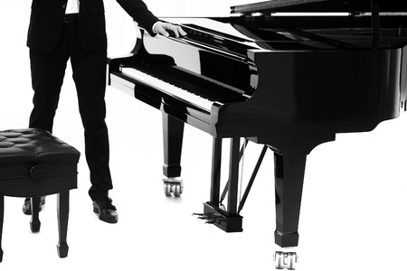 forte: Closeup view of one beautiful big shiny black open piano forte with white key board and male musician standing in studio isolated on white background, horizontal picture
