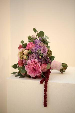 mazzo di fiori: Vista del primo piano di una bella fresca colorato bouquet di nozze mescolato con diversi fiori lilla viola porpora a colori rosa con fiocco rosso che si trova sul cubo bianco, immagine verticale coperta