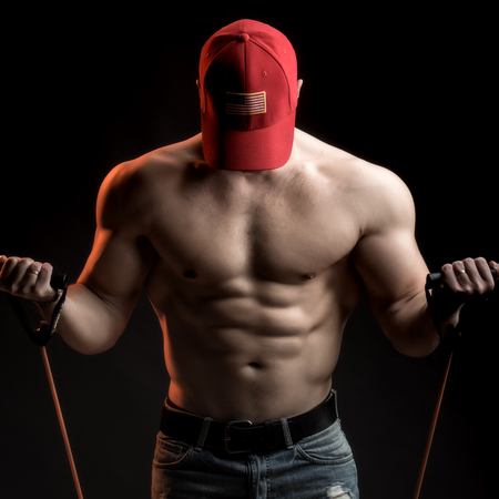 training device: One sexual strong young man with muscular body in red sport  cap standing posing holding training device in studio on black background, square picture Stock Photo