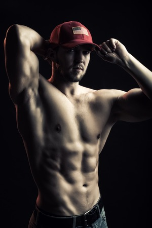 sexual anatomy: One sexual strong young man with muscular body in red sport  cap standing posing in studio on black background, vertical picture