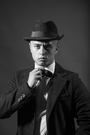 upper half: Portrait of retro fashion fifties young handsome serious frown man model looking straight dressed in black business suit hat holding tie studio on dark background black and white, vertical picture