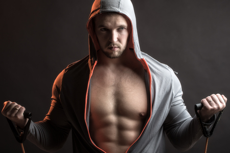 pectoral muscle: One sexual strong young man with muscular body in grey sport jacket with hood holding training device standing on studio black background, horizontal picture Stock Photo