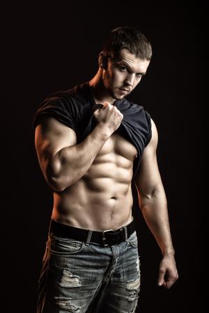 sexuel: Un sexuel fort beau jeune homme avec le corps musclé en blue-jeans avec une chemise sur l'épaule permanent posant en studio sur fond noir, verticale de l'image