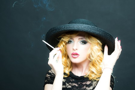 girl smoking: Portrait of one beautiful sensual sexy young retro blonde woman with curly hair and red lips in round black hat looking forward smoking cigarette on studio background, horizontal picture