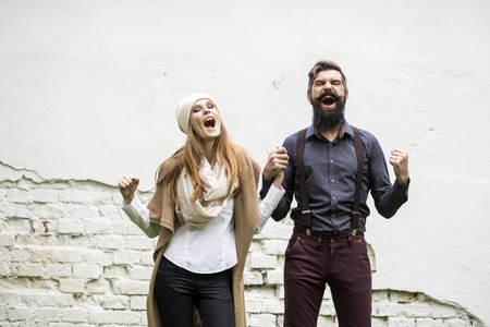 stylish couple: One beautiful stylish shouting couple of young woman and senior man with long black beard standing close to each other outdoor in autumn street on white brick wall background, horizontal picture Stock Photo