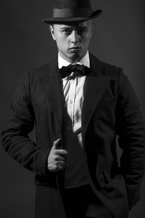 upper half: Portrait of retro style fifties respectable adorable elegant man dressed in suit with bow-tie and hat looking straight studio on dark background black and white, vertical picture Stock Photo