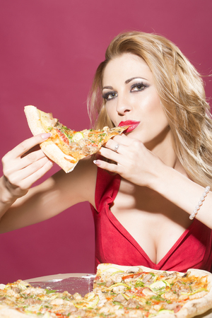 upper half: Portrait of attractive sensual young blonde woman with bright makeup wearing dress with deep decollete looking straight holding and eating piece of tasty pizza on red background indoor, vertical photo