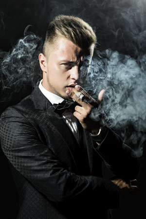 upper half: Attractive respectable important-looking man with fashion haircut small beard dressed in retro stylish suit whith bow-tie smoking havana looking straight on black background closeup studio, vertical